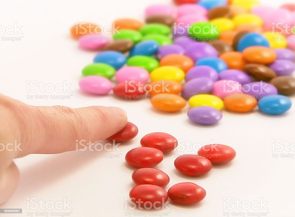 Close-up of the separation of red candies from multicolored royalty-free stock photo