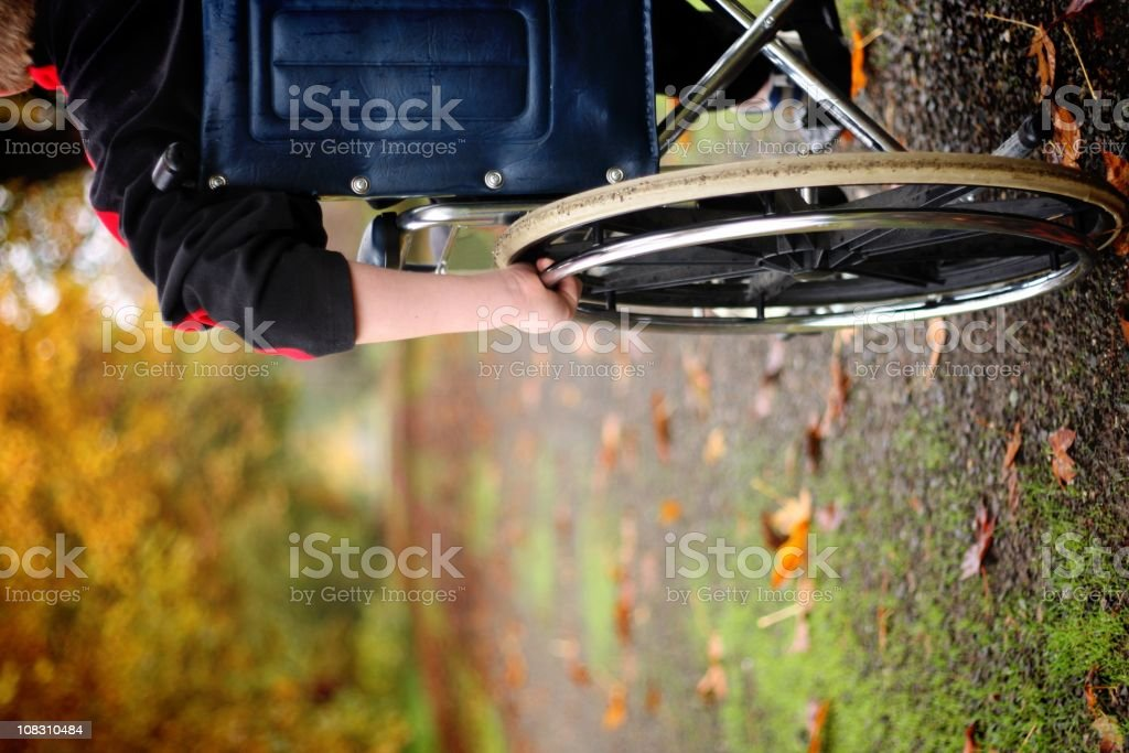 Close-up of the side of a wheelchair on a forest path royalty-free stock photo