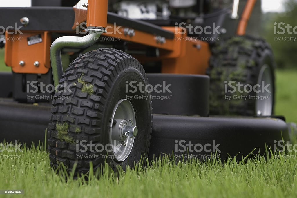 Close-up of the wheels and base of a working lawn mower stock photo