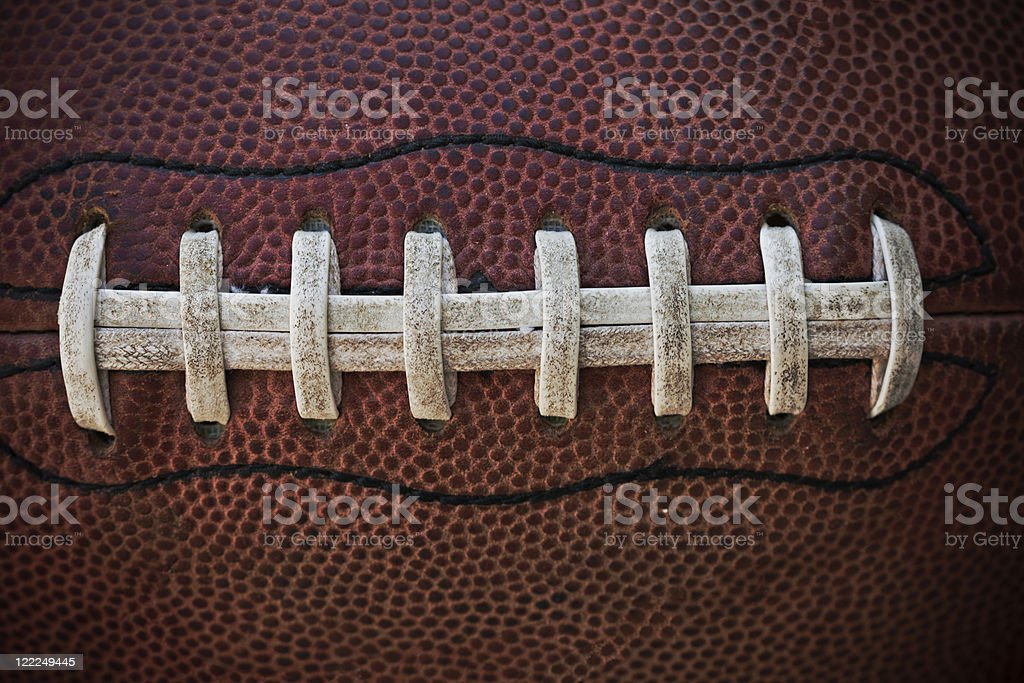 A close-up of the white stitches on an American football stock photo