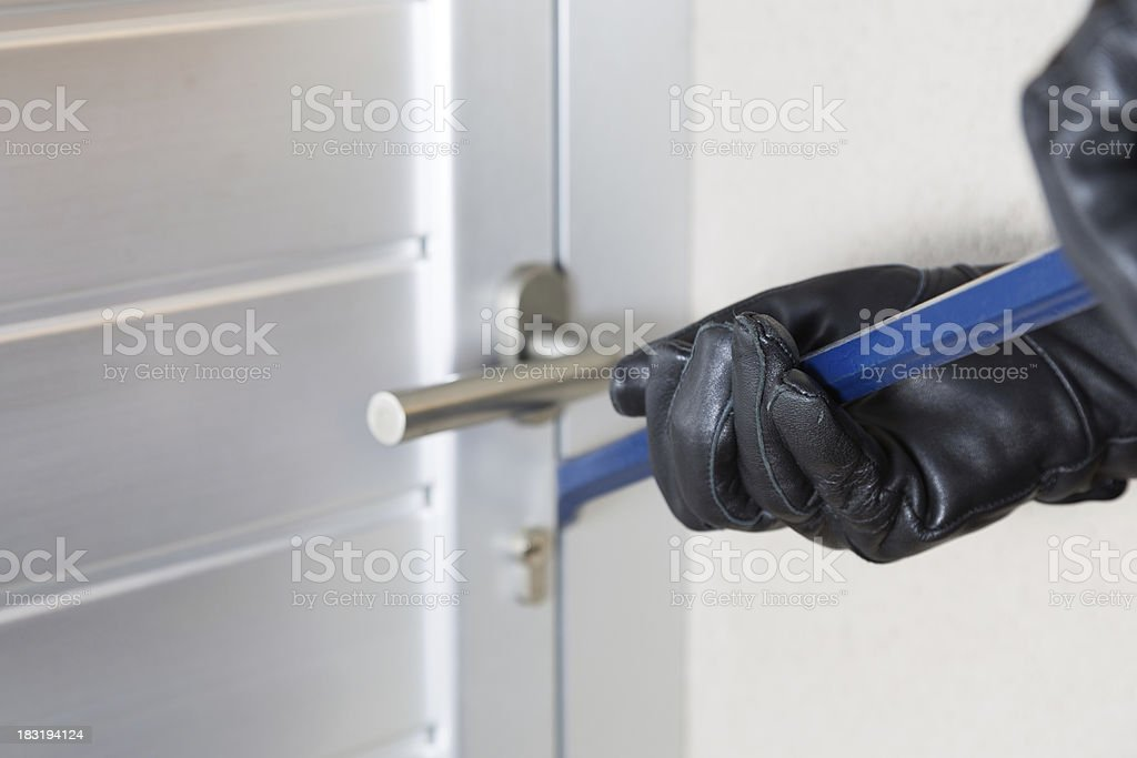 Close-up of thief using a bar of iron to break open a door stock photo