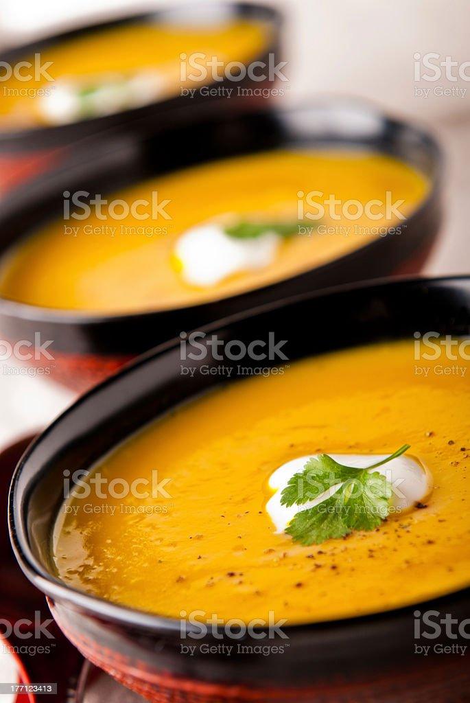 Close-up of three bowls of butternut pumpkin soup stock photo