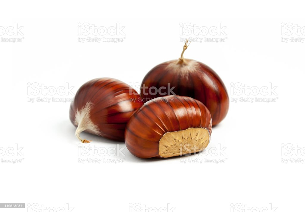 Close-up of three chestnuts on a white surface stock photo