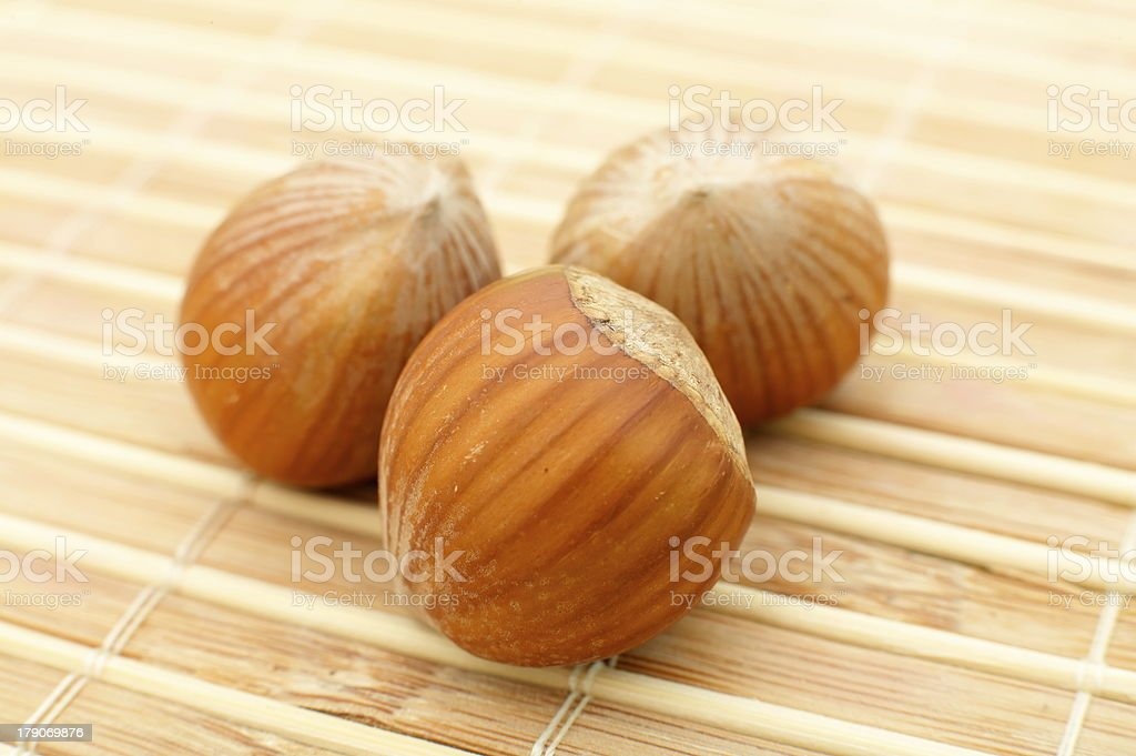 close-up of three hazelnuts on wooden background stock photo
