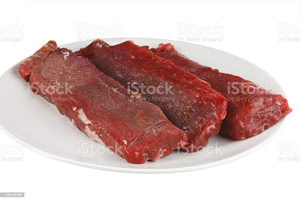 Close-up of three raw lamb strips on a white plate royalty-free stock photo