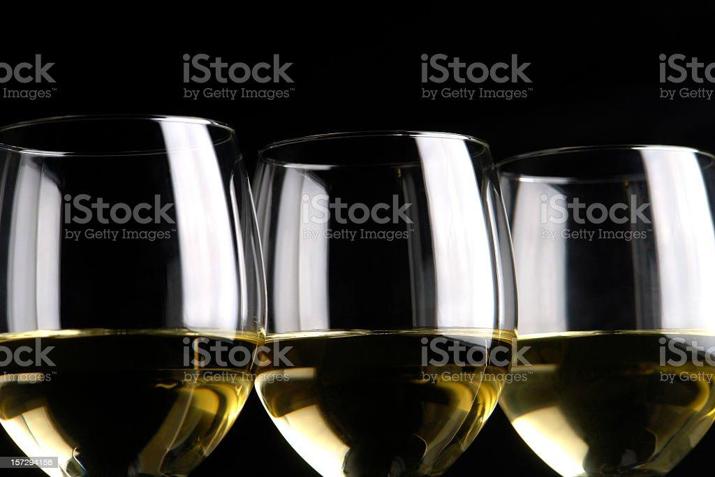 Close-up of three white wine glasses isolated on black, studio stock photo