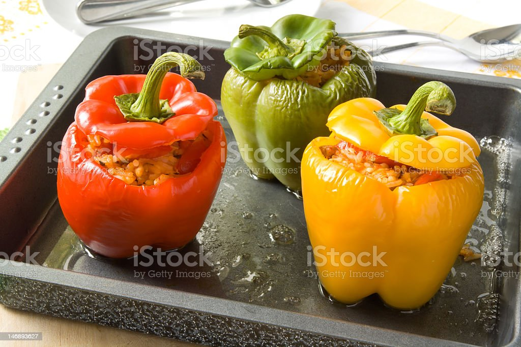 Close-up of three-color roasted stuffed capsicums on tray stock photo