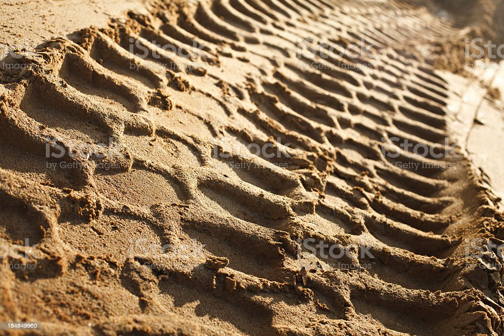 Close-up of tire tracks through wet sand stock photo