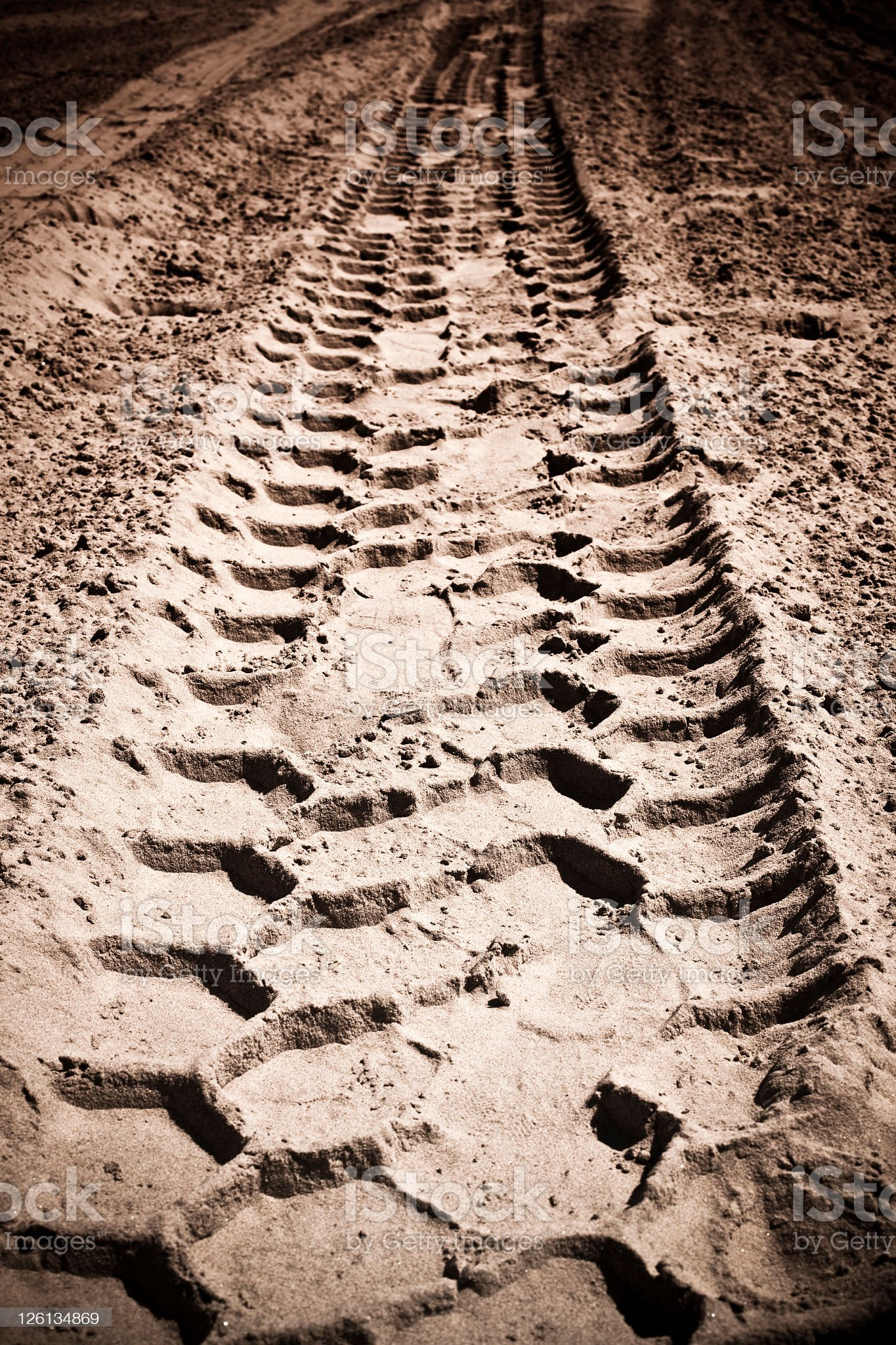 Close-up of tire tread tracks in the sand royalty-free stock photo