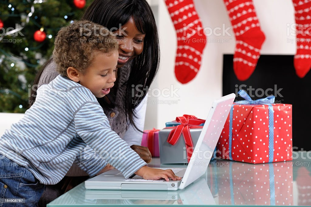 Close-up Of Toddler And Mother Using The Laptop At Christmas stock photo