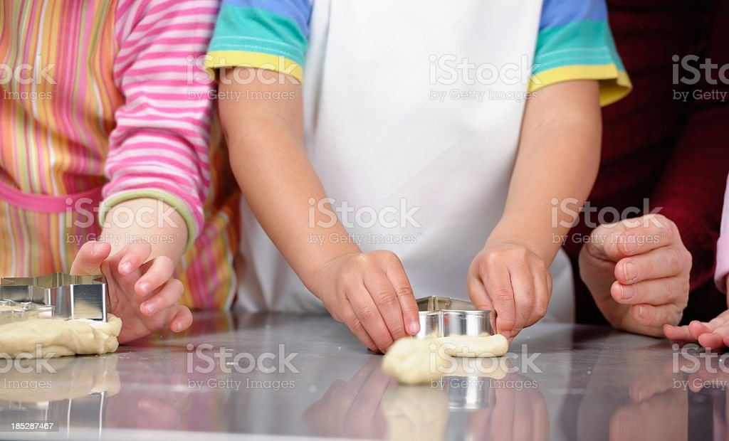 Close-up Of Toddlers And Carer Preparing Dough In The Kitchen stock photo