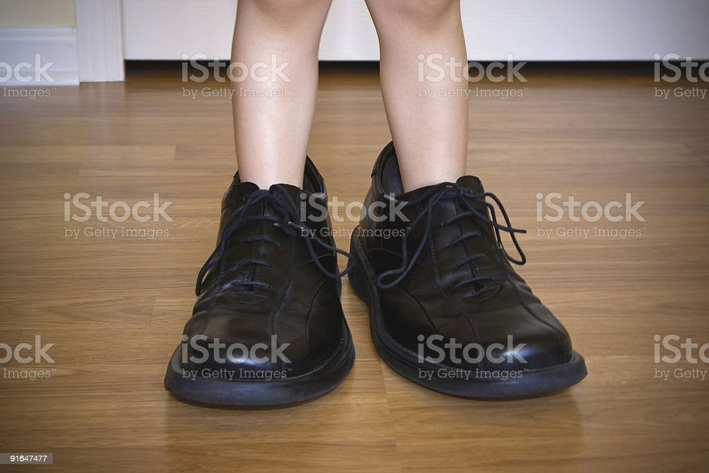 Closeup of Toddlers Legs Wearing Large Adult Shoes stock photo