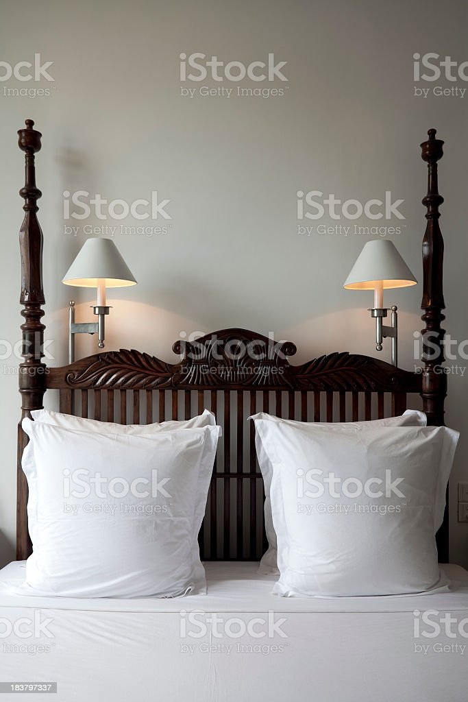 Closeup of top of a bed with lamps, posts and pillows royalty-free stock photo