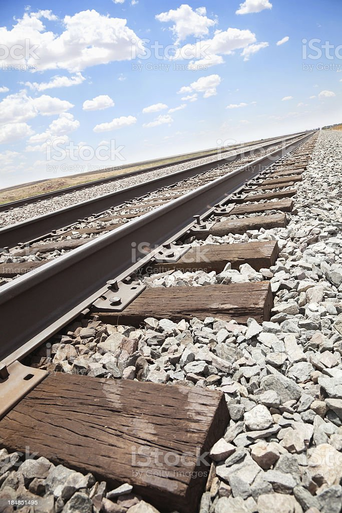 Closeup of train tracks heading out into the desert royalty-free stock photo