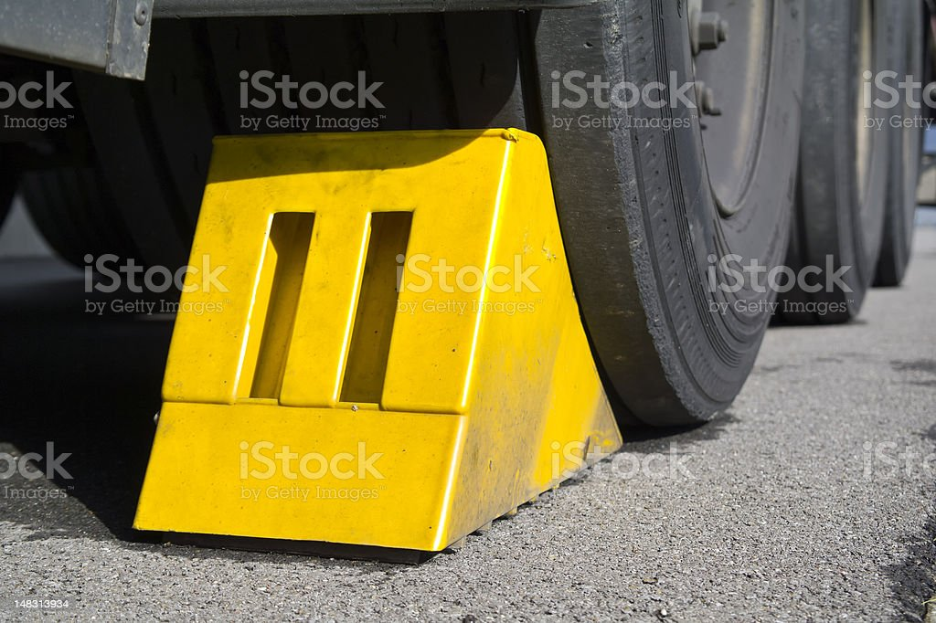 A close-up of truck wheels and a yellow wedge stock photo