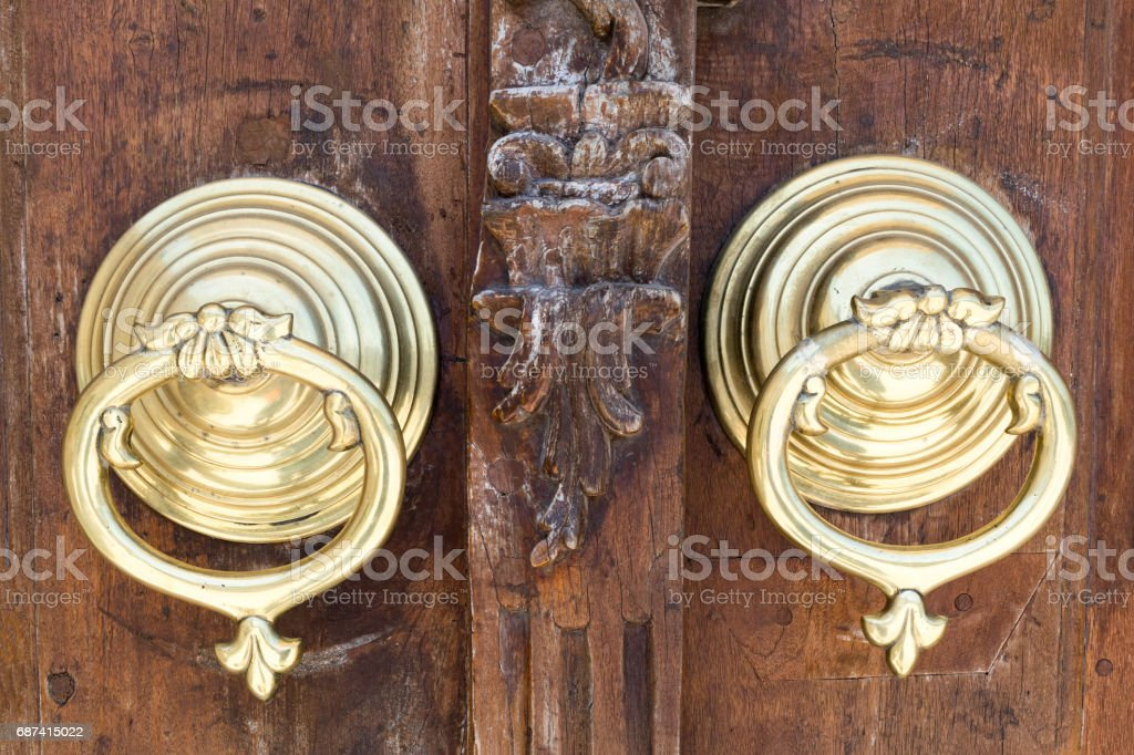 Closeup of two antique copper ornate door knockers over an aged wooden ornate door stock photo
