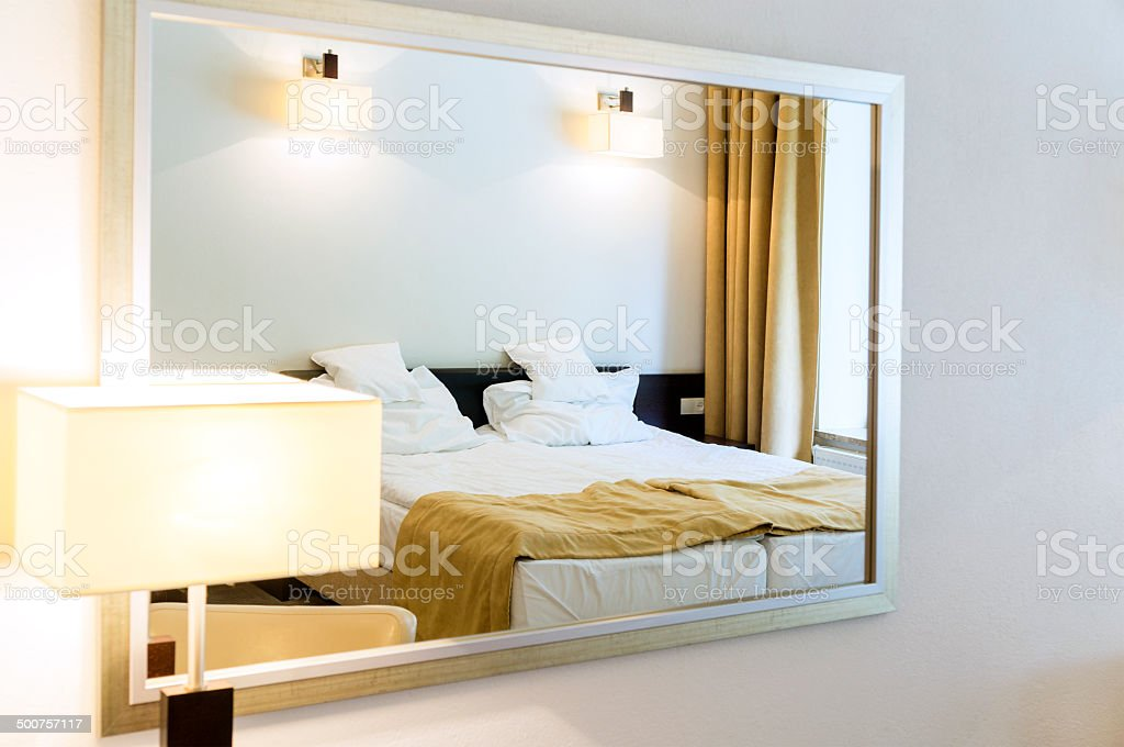 Close-up of two beds bedroom reflects in mirror with frame stock photo