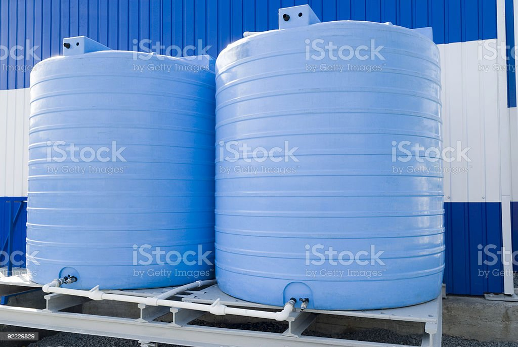 A closeup of two blue water storage tanks royalty-free stock photo