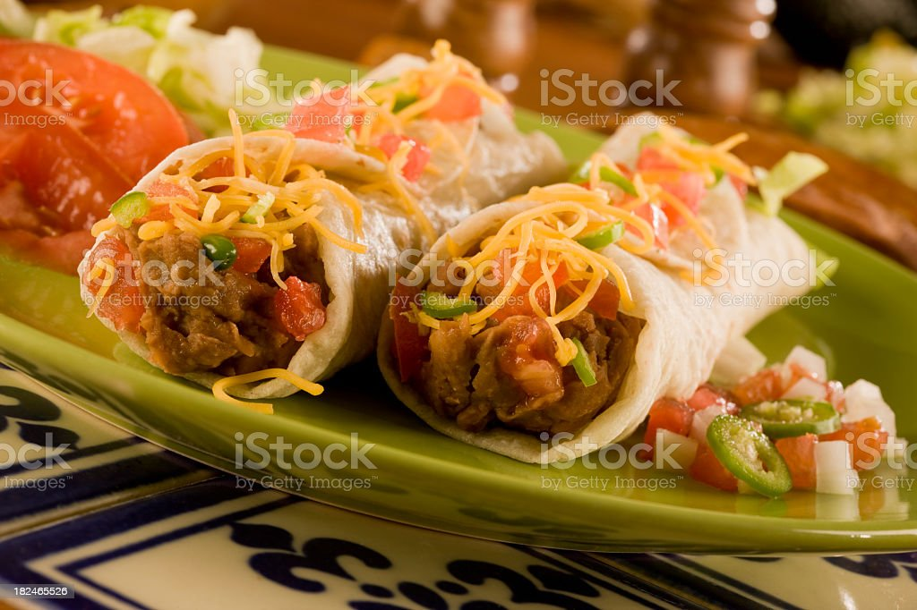 Close-up of two burritos on a green plate stock photo