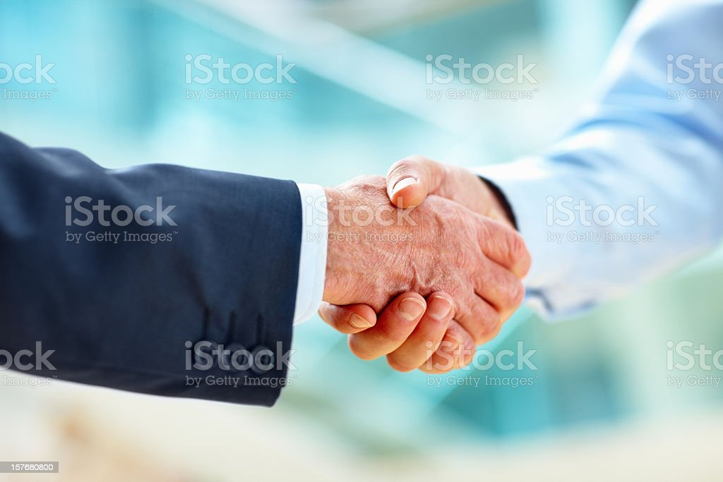 Closeup of two business executives shaking hands over a deal royalty-free stock photo