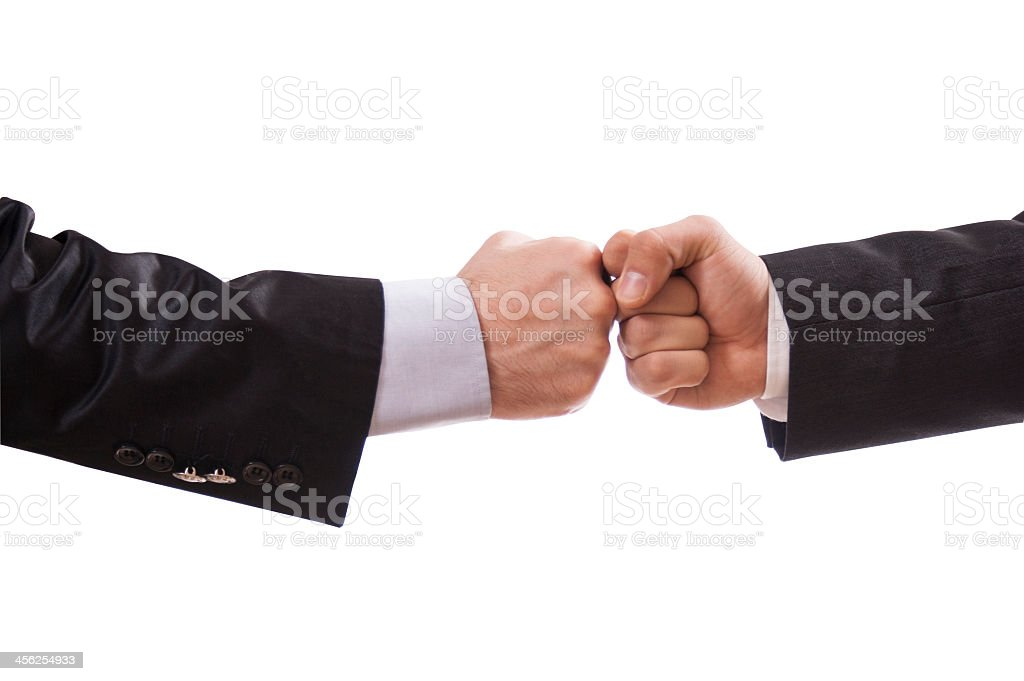 Close-up of two businessman bumping fists stock photo