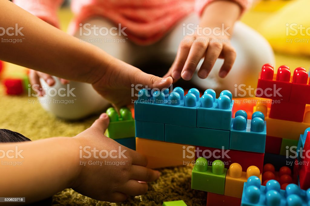 Close-up of two children playing with toy blocks. stock photo