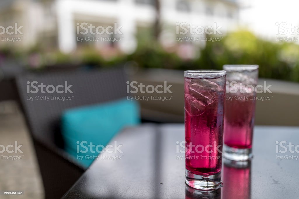 Close-up of two glasses of bright pink raspberry cocktails shot outside on a bar patio. stock photo