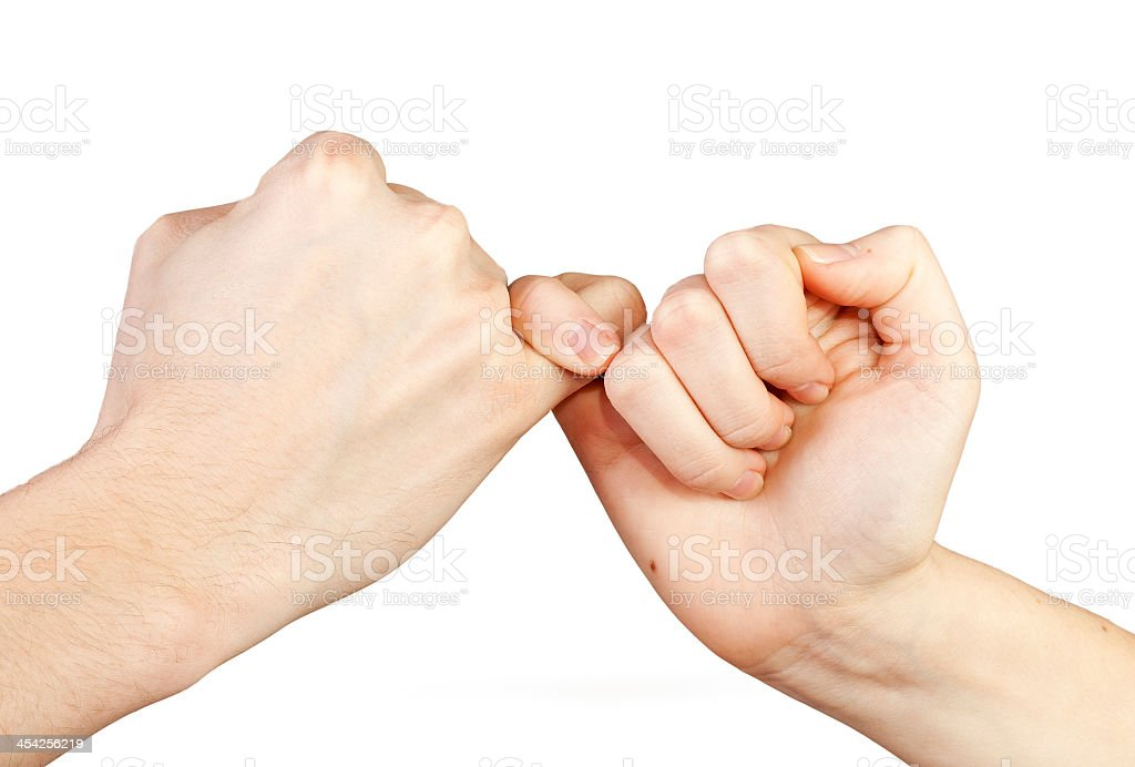 Close-up of two hands doing a pinky swear gesture stock photo