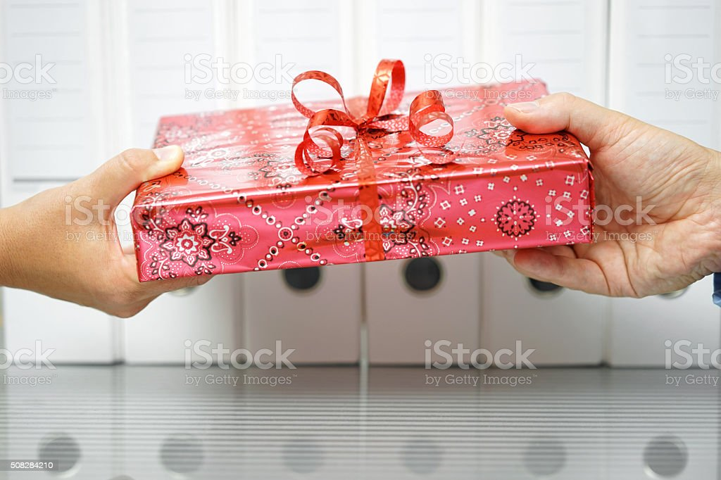 closeup of two hands exchanging gift in office