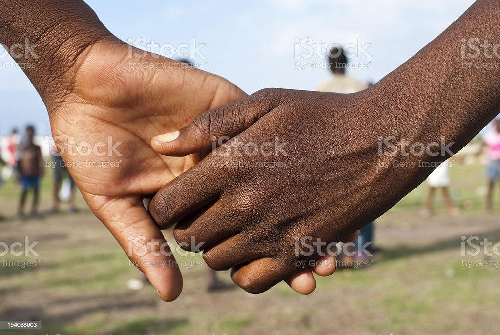 Close-up of two people holding hands in a field stock photo