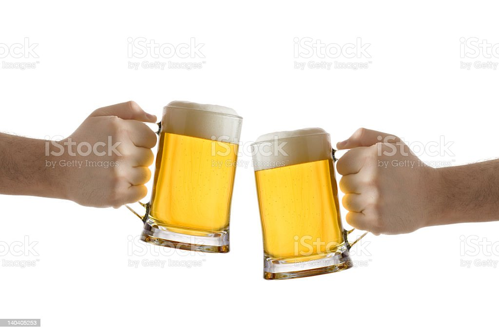 Close-up of two peoples hands with full beer glasses stock photo