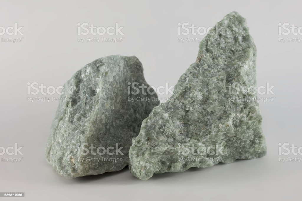 Close-up of two raw jade mineral stones, isolated on white background stock photo