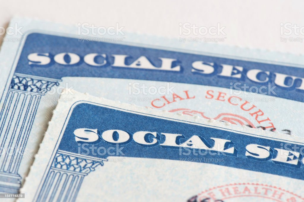 Close-up of two social security cards over a white backdrop stock photo