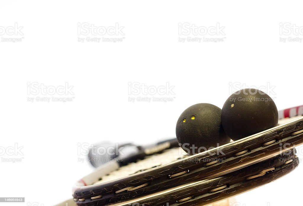 Close-up of two squash rackets and balls over white backdrop stock photo