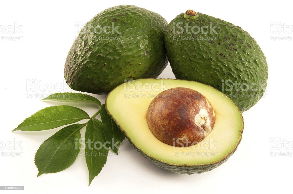 Close-up of two whole and one halved avocado royalty-free stock photo