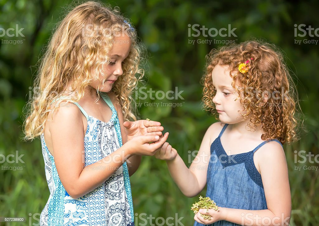 Close-Up of Two Young Girls With Monarch Butterfly Caterpillar stock photo