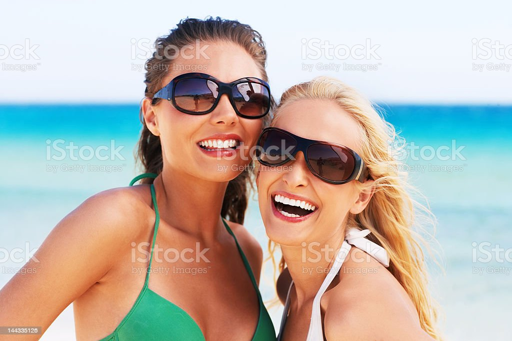 Close-up of two young women smiling on the beach royalty-free stock photo