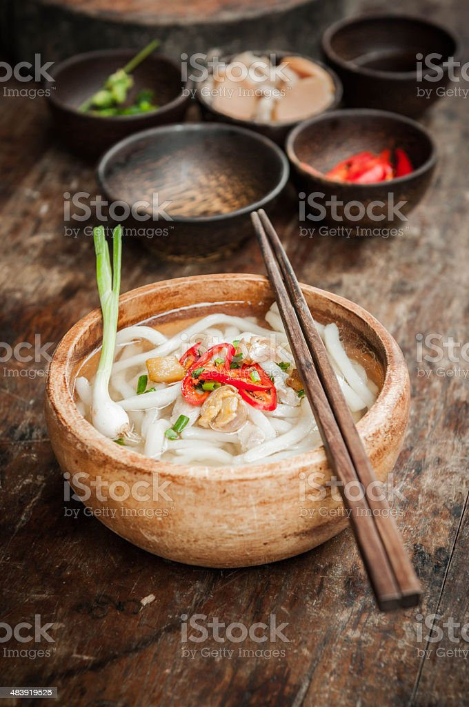 closeup of udon noodle in wood bowl on wooden floor stock photo