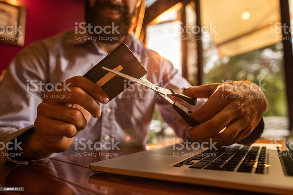 Close-up of unrecognizable businessman cutting credit card with scissors. stock photo