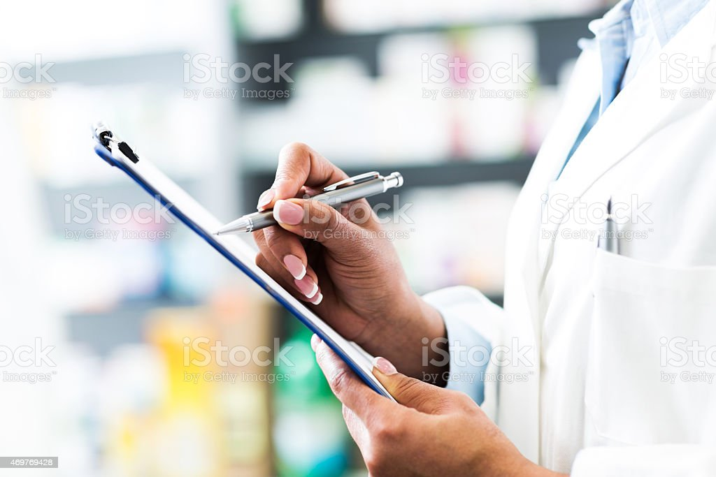 Close-up of unrecognizable doctor writing medical chart. stock photo
