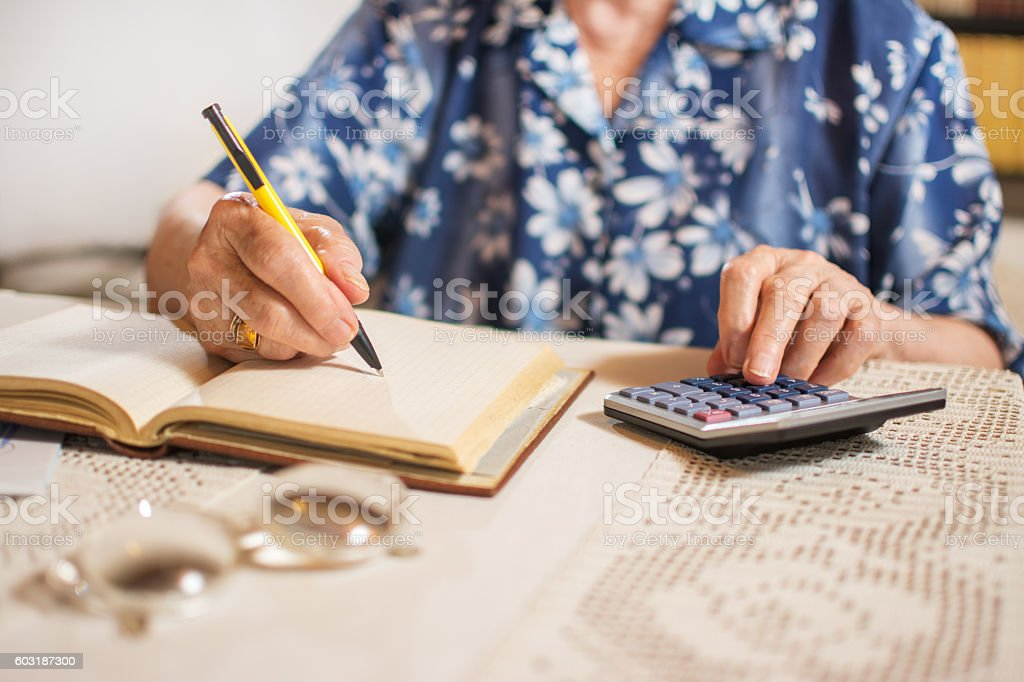 Close-up of unrecognizable senior woman doing finances at home. stock photo