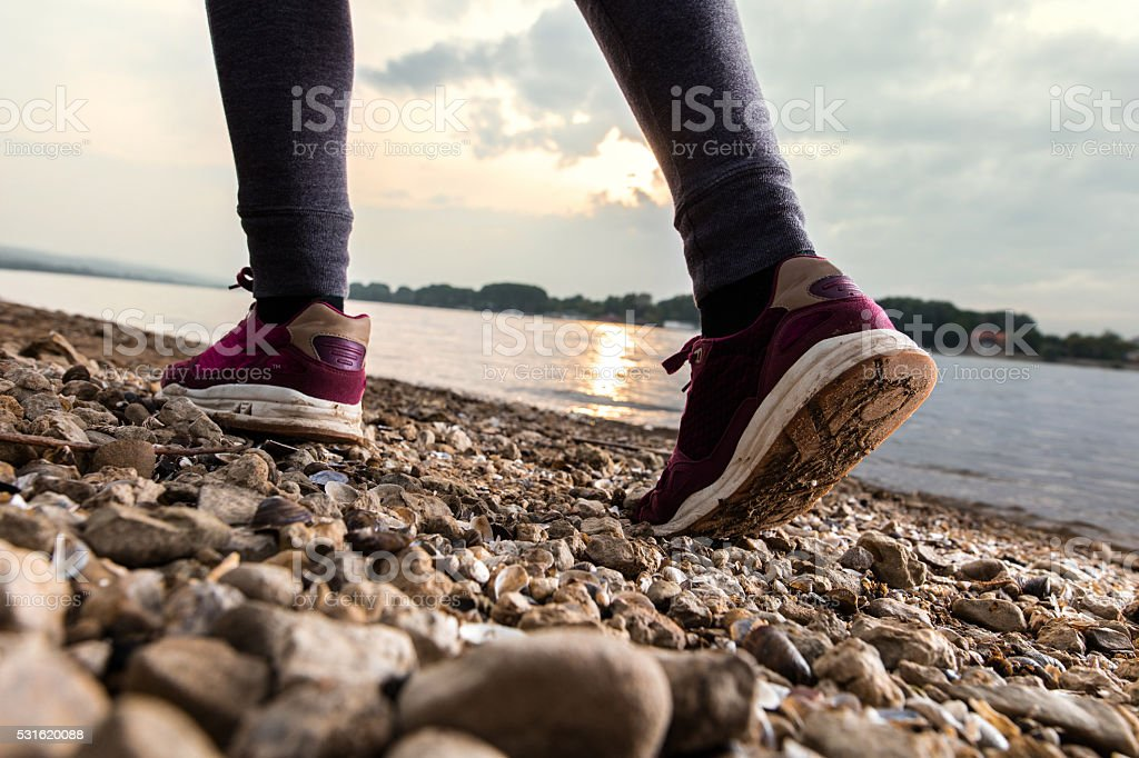 Close-up of unrecognizable woman walking on beach by the river. stock photo