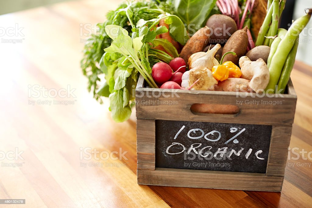 Close-up of various vegetables in wooden crate, 100% organic sign stock photo