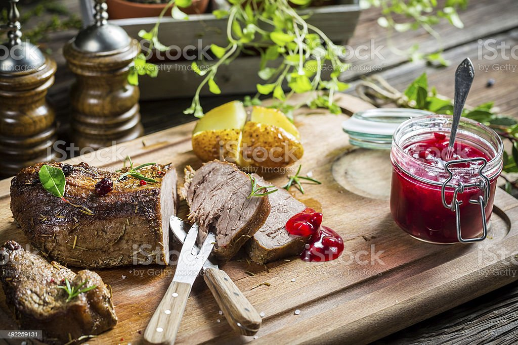 Closeup of venison with cranberry sauce and vegetables royalty-free stock photo