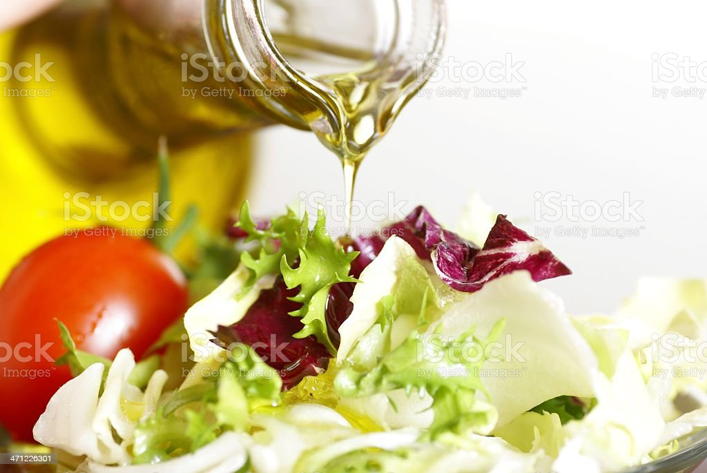 Close-up of virgin olive oil being poured on garden salad stock photo