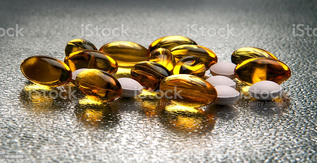 Close-up of vitamin E and D pills on shiny surface royalty-free stock photo