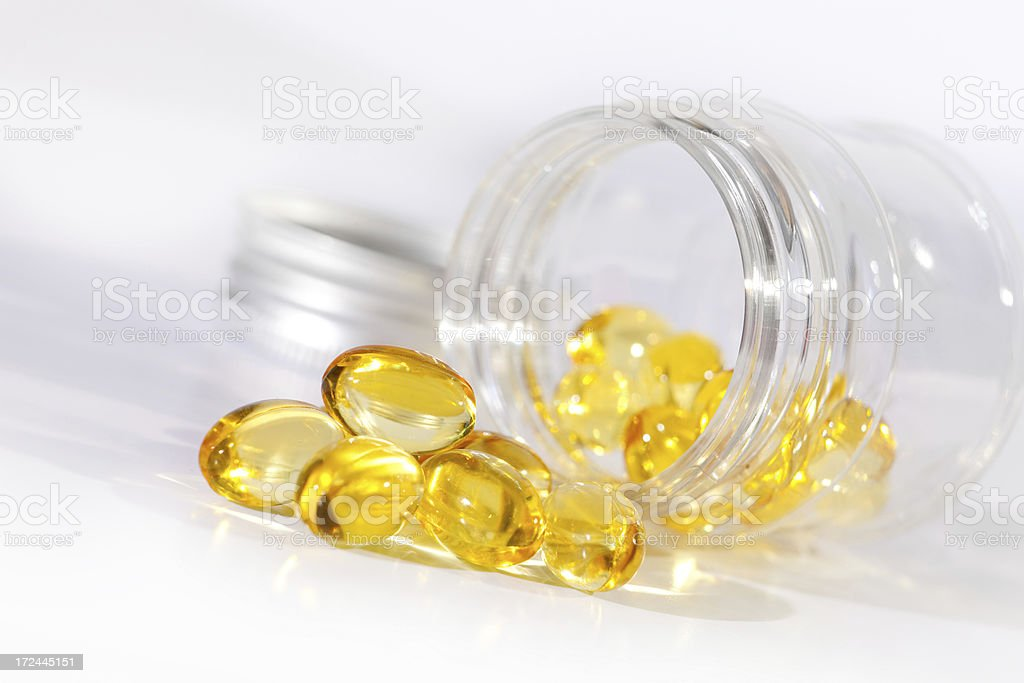 Close-up of vitamin gel pills coming out from medicine bottle stock photo