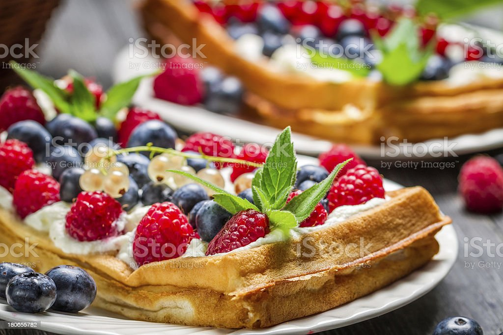 Closeup of waffels with cream and berry fruits royalty-free stock photo