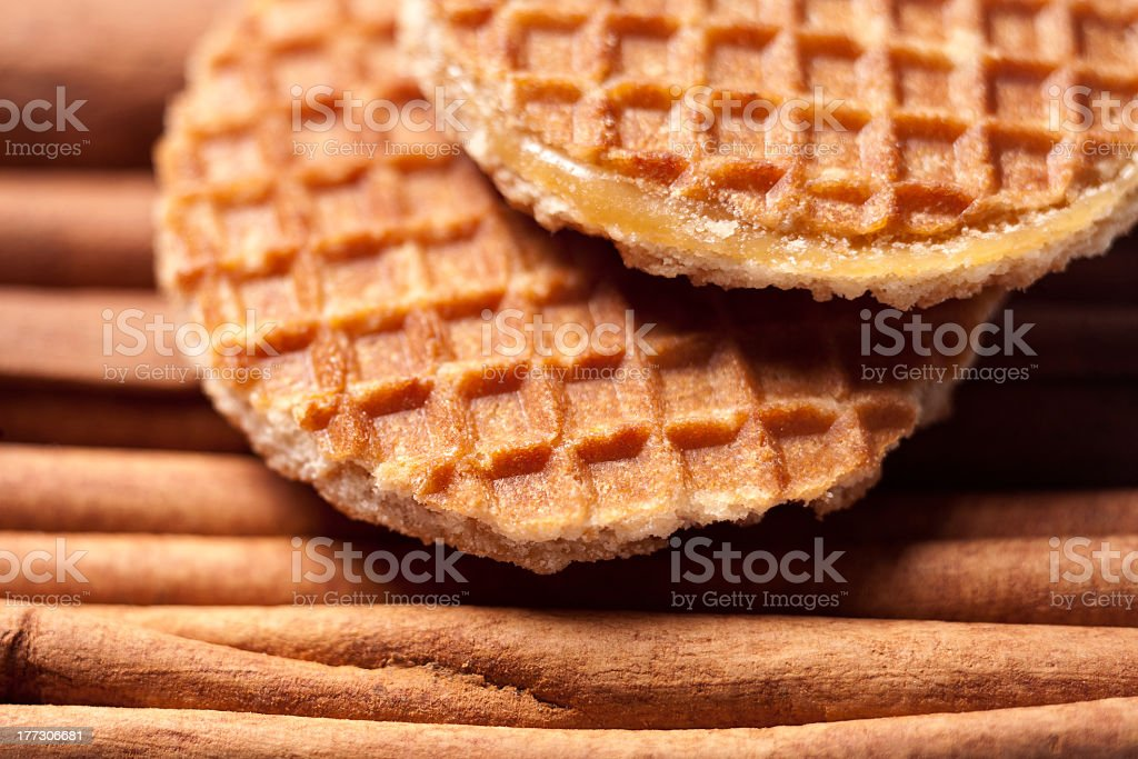 Close-up of waffle cookies on top of cinnamon sticks stock photo