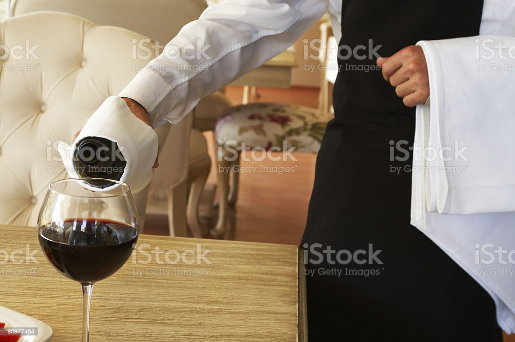 Close-up of waiter serving red wine in nice restaurant royalty-free stock photo